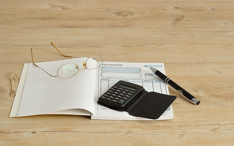 An Invoice Book With Glasses, Calculator And Pen